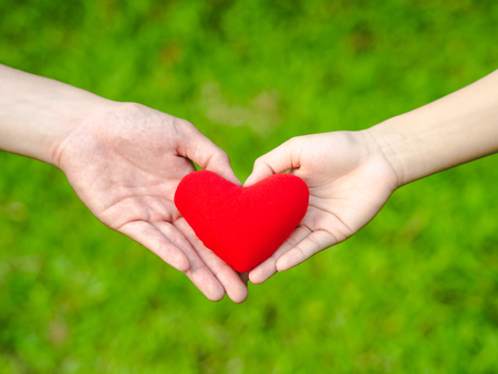Man and woman heart shape hands hold the red heart. Couple, Love, Valentine'sDay Concept.