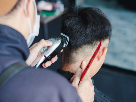 Close up barber using hair clipper and comb to cut the hair in the barber shop.