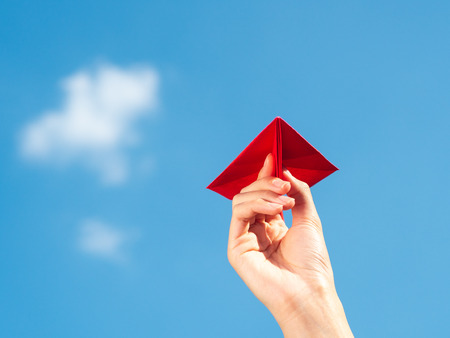 Woman Hand holding red paper rocket with blue sky background. freedom concept 版權商用圖片