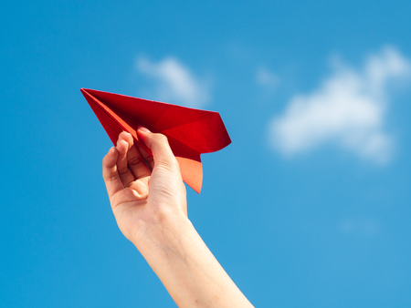 Woman Hand holding red paper rocket with blue sky background. freedom concept 写真素材