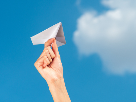 Woman Hand holding paper rocket with blue sky background. freedom concept