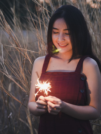 Happy cute girl holding a sparkler in the dry grass field. 版權商用圖片
