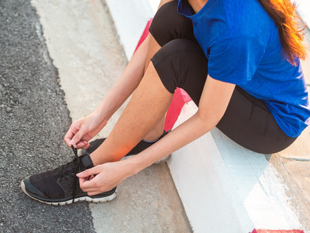 Young woman runner tying shoelace before running. Archivio Fotografico