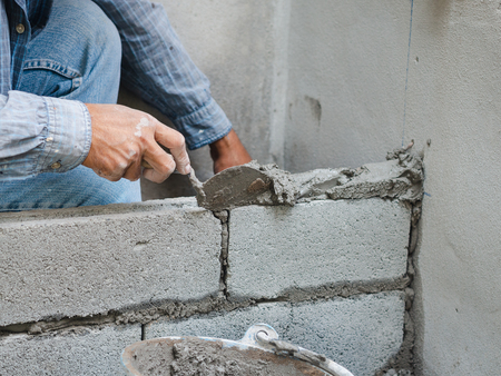professional construction worker laying bricks with cement.