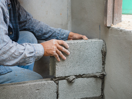 professional construction worker laying bricks with cement. 版權商用圖片 - 118937995