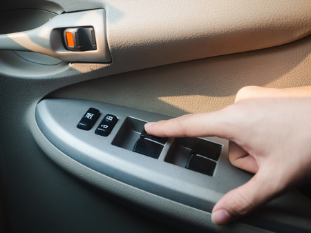 Closeup Driver's hand pressing Car window controls button. 版權商用圖片