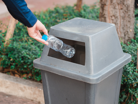 Closeup of man hand throwing empty plastic water bottle in a bin.