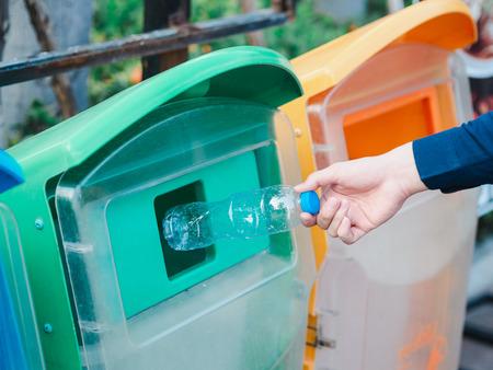 Primo piano della mano dell'uomo che getta una bottiglia d'acqua di plastica vuota nel bidone di riciclaggio.