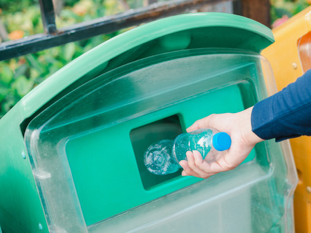 Closeup of man hand throwing empty plastic water bottle in recycling bin.