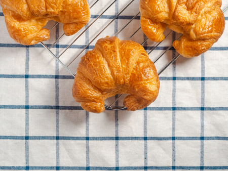 Top view of fresh croissants on checkered towel.