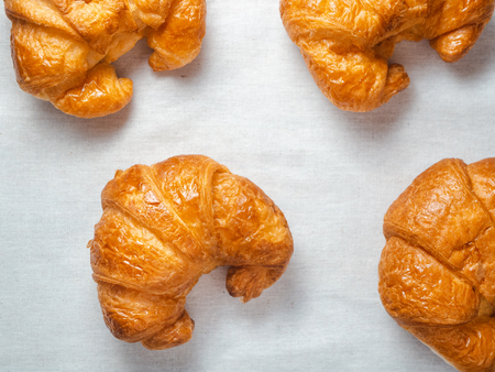 Top view of fresh croissants on white towel.