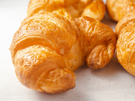 Close up of fresh croissants on white towel.