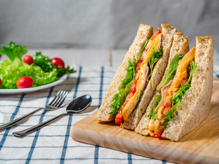 Close up of Sandwich with ham, cheese, tomatoes, lettuce, and toasted bread on the  wooden cutting board.