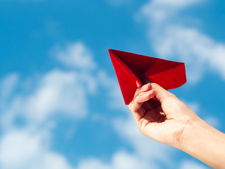 Woman Hand holding red paper rocket with blue sky background. freedom concept 版權商用圖片 - 118938429