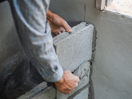 professional construction worker laying bricks with cement. 版權商用圖片 - 118938434