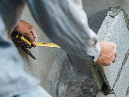 professional construction worker uses measuring Tape for measure and laying bricks with cement. 版權商用圖片