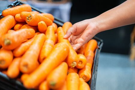 Woman hand picking up carrot in supermarket. woman shopping in a supermarket and buying fresh organic vegetables. Healthy eating Concept.