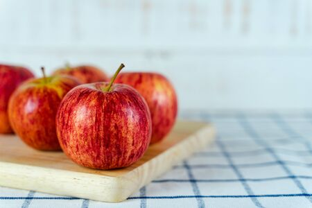 Fresh red apples on wooden cutting board and towel background.