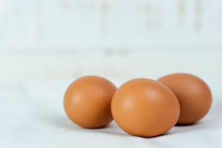 Close-up of raw chicken eggs on white wooden background.
