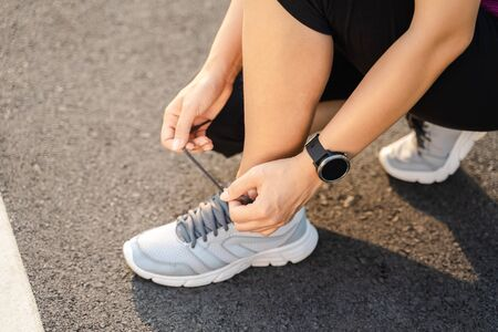 closeup of young woman runner tying her shoelaces. healthy and fitness concept.