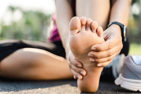 Running injury leg accident- sport woman runner hurting holding painful sprained ankle in pain. Female athlete with joint or muscle soreness and problem feeling ache in her lower body. 版權商用圖片
