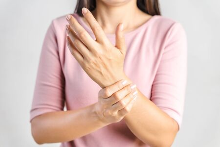 Closeup young woman holds her wrist on white background. hand injury, feeling pain. Health care and medical concept.