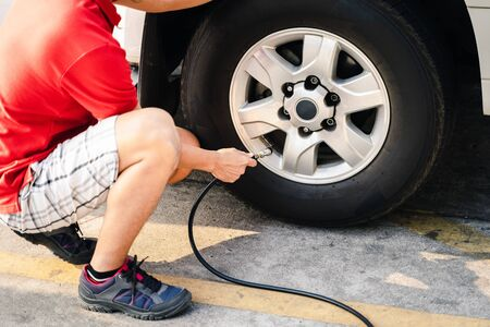 Close up of asian man inflating tire in the gas station. 版權商用圖片