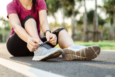 closeup of young woman runner tying her shoelaces. healthy and fitness concept. 版權商用圖片 - 141836569