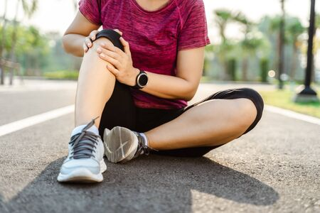 knee Injuries. sport woman with strong athletic legs holding knee with her hands in pain after suffering muscle injury during a running workout training on Running Track. Healthcare and sport concept.