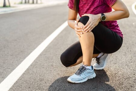 knee Injuries. sport woman with strong athletic legs holding knee with her hands in pain after suffering muscle injury during a running workout training on Running Track. Healthcare and sport concept. 版權商用圖片 - 141837419