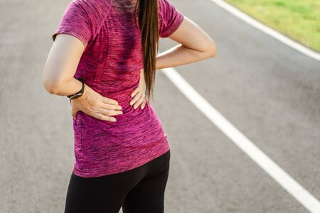 Cloaeup woman runner on running track touching hurt back with painful injury