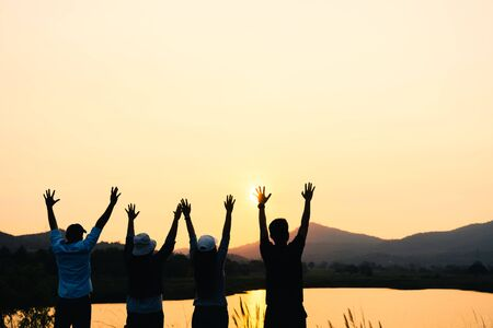 A group of people with raised arms looking at sunrise on the mountain