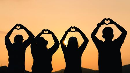 A group of people with raised arms and make hand to the heart shape looking at sunrise on the mountain