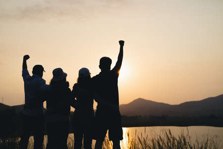 group of people with raised arms looking at sunrise on the mountain background. Happiness, success, friendship and community concepts.