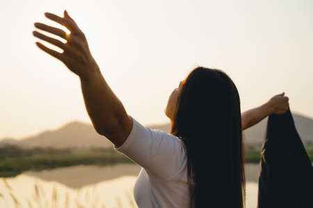 Happy business woman spreading arms and watching the mountain silhouette. Business success concept, freedom emotions 版權商用圖片