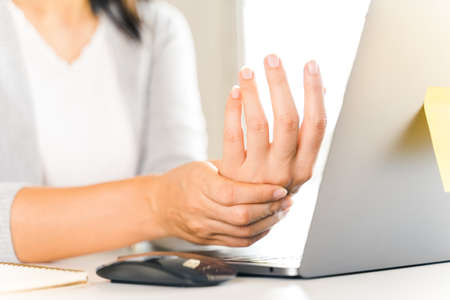 Closeup woman holding her hand pain from using computer long time. Office syndrome concept.