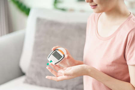 Asian woman checking blood sugar level by Digital Glucose meter, Healthcare and Medical, diabetes, glycemia concept