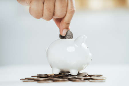 Close up of woman hand putting money coin into piggy bank for saving money. saving money and financial concept