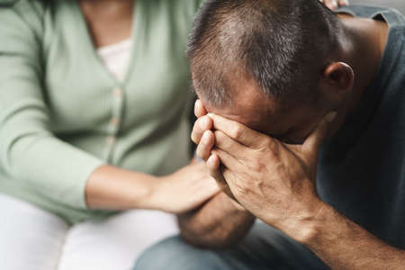 Female Psychologist, friend or family sitting and put hands on the shoulder for cheer up to mental depress man, Psychologist provides mental aid to the patient. PTSD Mental health concept