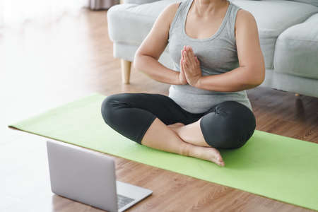 Mature Asian chubby fat woman sitting on the floor in living room practice online yoga lesson with the computer. female having meditate training class on the laptop.