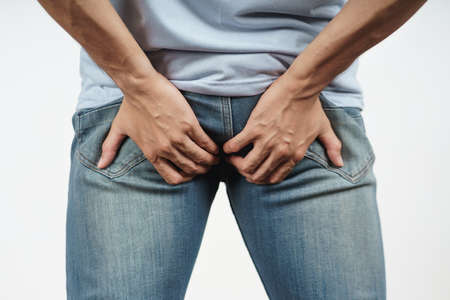 Young Man holding his bottom because Diarrhea, Hemorrhoids, constipation. Health care and medical concept.