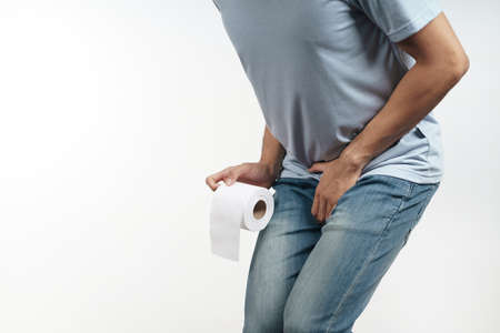 Young man holding his crotch and tissue paper suffering from Diarrhea, incontinence, prostatitis, venereal disease. Healthcare concept.
