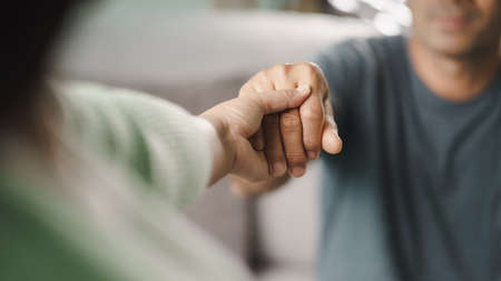 Female friend or family holding hands during cheer up to mental depress man, Psychologist provides mental aid to patient. PTSD Mental health concept. 免版税图像