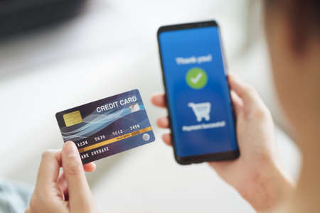 Young woman holding credit card and using smart phone for online shopping, internet banking, e-commerce, spending money, working from home concept