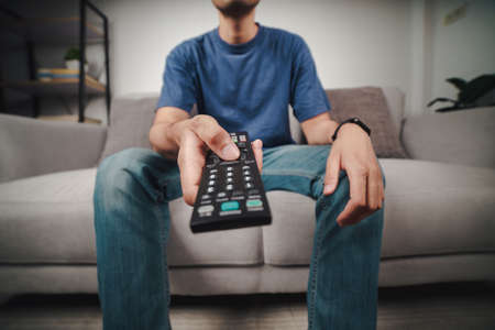 Man hold and press the TV remote controller button sitting on the couch.
