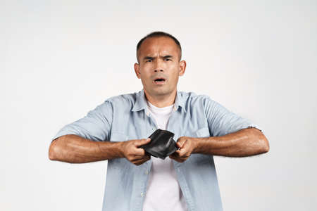 Upset mature man holding and upside down his empty wallet on white background. financial crisis, bankruptcy, no money, bad economy Concept.