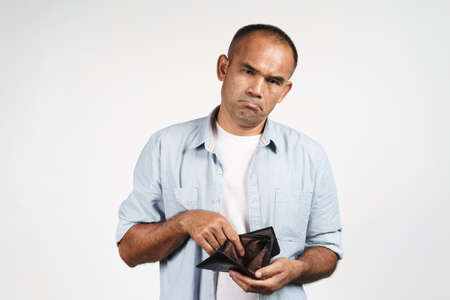 Upset mature man holding and looking inside his empty wallet on white background. financial crisis, bankruptcy, no money, bad economy Concept. 免版税图像