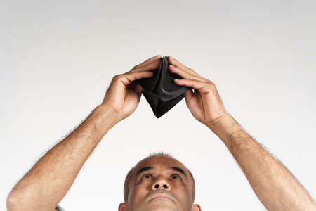 Upset mature man holding upside down and looking inside his empty wallet on white background. financial crisis, bankruptcy, no money, bad economy Concept. 免版税图像