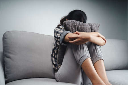 Unhappy lonely sad woman is sitting on the couch and hiding her face on a pillow, depression concept