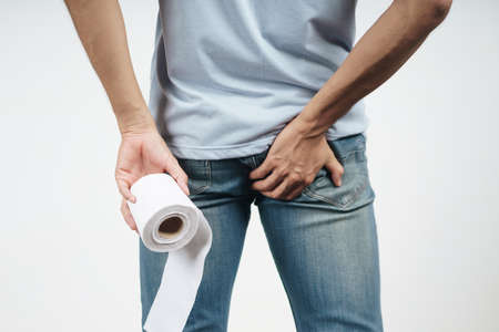 Young Man holding his bottom and tissue paper because Diarrhea, Hemorrhoids, constipation. Health care and medical concept. 免版税图像